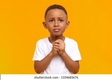 Poverty, grief and need concept. Studio shot of mournful frustrated little African boy holding hands clapsed together and looking up, pleading, begging for money. Human facial expressions and emotions