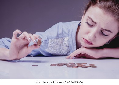 Poverty and low salary concept. Young frustrated and desperate Woman counting small money.