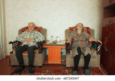 poverty old couple sitting on armchair in the room