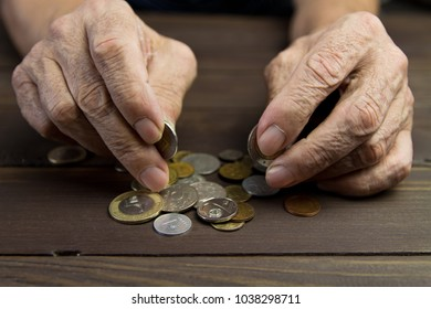 Poverty.Hands of beggar with few coins. The concept of poverty . An elderly person on pension holds coins on wooden table background