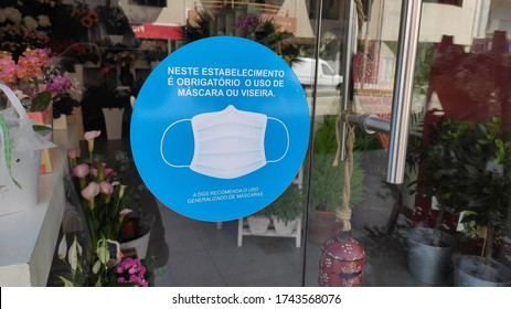 """Povoa de Varzim, Portugal - May 28 2020: Sign in store window during COVID-19 outbreak. Text saying """"The use of a mask or face shield is obligatory in this establishment"""" (English translation)"""