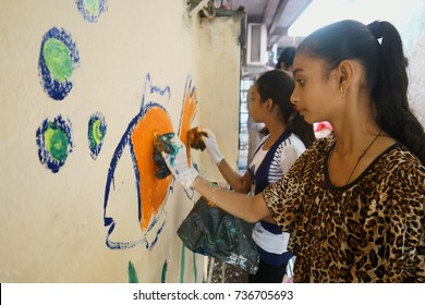 POWAI, MUMBAI, MAHARASHTRA, INDIA - OCTOBER 16, 2017 - Young slum girls are seen painting a wall in their chawl area, as part of a clean up initiative taken up by their school.