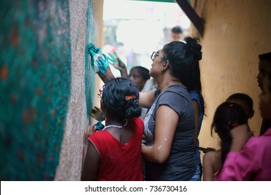 POWAI, MUMBAI, MAHARASHTRA, INDIA - OCTOBER 16, 2017 - A social worker/ artist is seen painting a wall in a chawl area, as part of a clean up initiative taken up for the rehabilitation of slum kids.