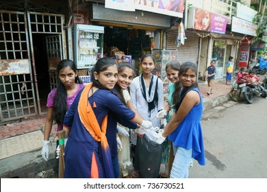 POWAI, MUMBAI, MAHARASHTRA, INDIA - OCTOBER 16, 2017 - Young slum girls are seen collecting garbage found on the streets in their chawl area, as part of a clean up initiative taken up by their school.