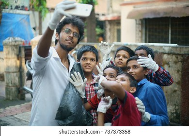 POWAI, MUMBAI, MAHARASHTRA, INDIA - OCTOBER 16, 2017 - A social worker is taking a selfie with young girls collecting garbage on the streets, as part of a clean up initiative taken up by their school.