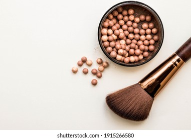 Powder brush and mixed colored glow face pearls blush on bright background. Top view with copy space.