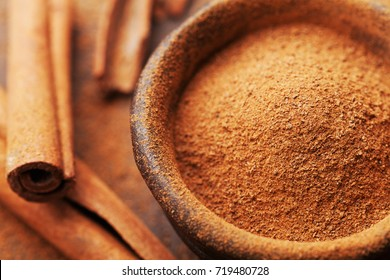 Powder cinnamon and sticks and on brown rustic background. Aromatic spices.