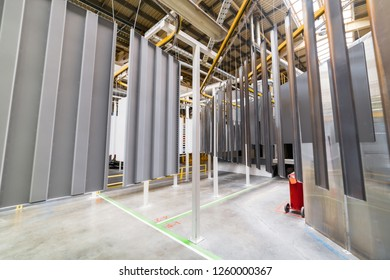 Powder coating line. Metal panels are suspended on an overhead conveyor line. Painting products in an electrostatic field.