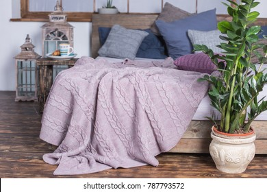 powder color knitted blanket on the bed