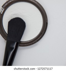powder makeup and brush and white background