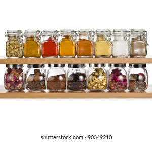 powder spices and herbal tea in glass bottle on a shelf isolated on white background