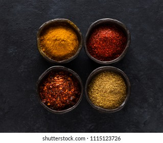 Powder spices and herbs in bowls on a black concrete background, top view