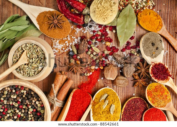 powder spices on spoons in wooden background