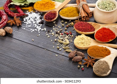 Powder spices in the spoons in black wooden table background