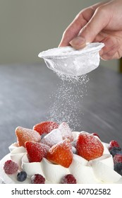 Powder of sugar is hung on a strawberry cake.