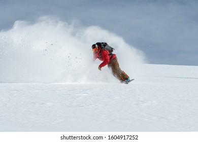 Powder turn from snowboarder in the backcountry