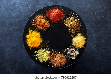 Powder of various spices and herbs on a black concrete background
