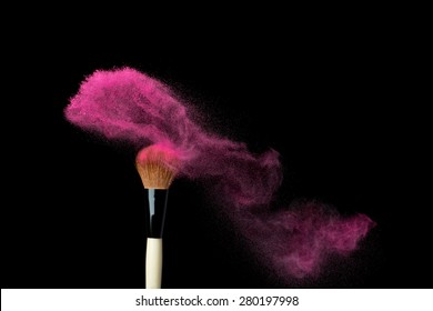 powderbrush on black background with pink powder splash close up