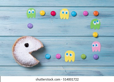 Powdered donut with smiley face and colored smarties and ghosts, wooden background