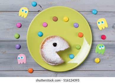 Powdered donut with smiley face eating colored smarties or candy drops, wooden background