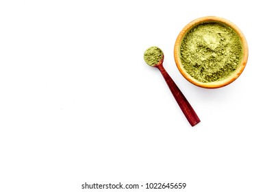 Powdered matcha green tea in bowl and scattered on white background top view copy space