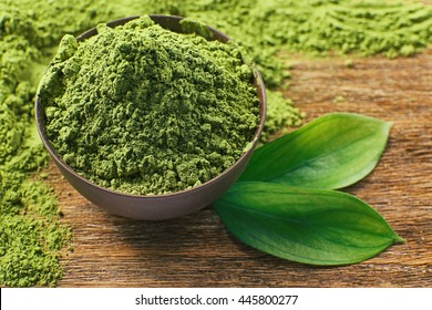 Powdered matcha green tea on wooden table