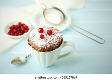 Powdered mug cake with cranberry on table