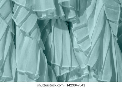 Powdered pastel mint color chiffon fabric folds.Turquoise dress with ruffles and frills.