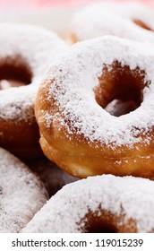 Powdered sugar crusty donuts closeup