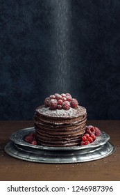 Powdered Sugar Falling on Stack of Dark Chocolate Pancakes with Raspberries and Red Currants on Silver Plate