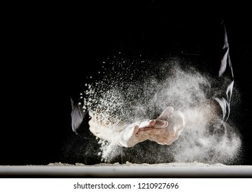 Powdery flour flying into air as man in black chef outfit wipes off his hands over white table covered in flour