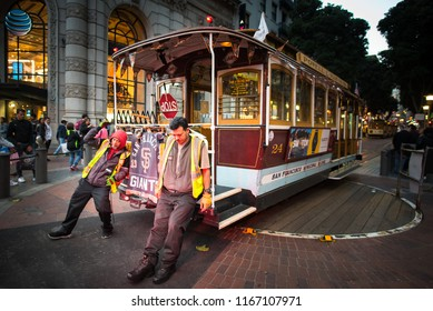 Powell & Market cable car turntable terminal, San Francisco, CA / USA - May 26 2018: Two strong men manually rotate heavy famous San Francisco tram - U.S. National Historic Landmark tourist attraction