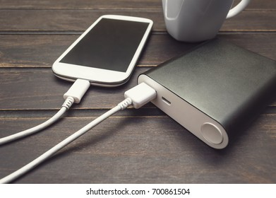 Power bank charging a smart phone next to a cup of coffee.