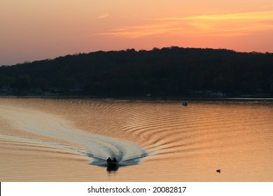 Power Boat coming back with a sunset background