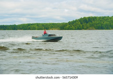 power boating on background of lake, green forest and blue sky with clouds. man in boat. motorboats on lake