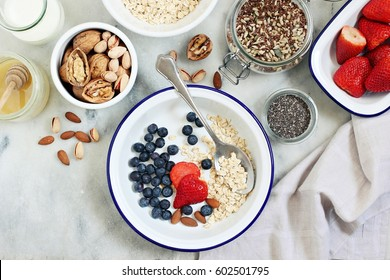 Power breakfast ingredients for preparing of overnight oats with fresh berries and  various of super foods topping.