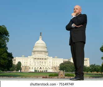 Power broker type in a suit, hand on chin standing in front of the U.S. Captiol building, downtown Washington, DC, USA.