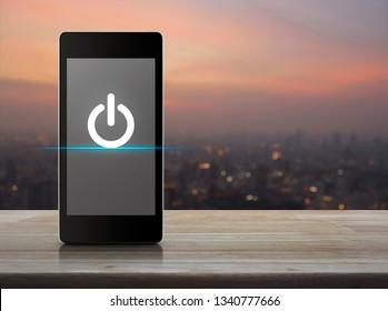 Power button flat icon on modern smart mobile phone screen on wooden table over blur of cityscape on warm light sundown, Start up business online concept