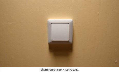 Power button on a yellow wall