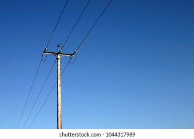 Power cables and post against a blue sky