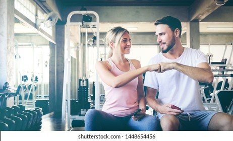 Power concept. Image of sporty people giving fist bump to each other as symbol of their partnership. Woman show up mobile phone to handsome fitness man. teamwork sport agreement concept.