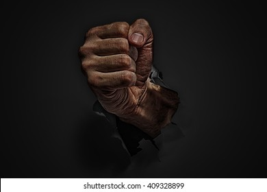 Power concept. Man fist punching through black paper