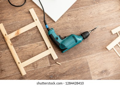 Power drill and wood products and constructions lay on a floor ready to work