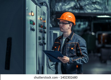 power engineer checks equipment at work and records readings