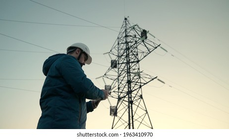Power engineer in protective white helmet checks power line online using computer tablet, remote access to energy system, for control and safety. High voltage electrical lines at sunset. clean energy