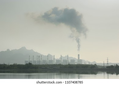 power generating station with smokestacks and wetland or reservoir. Power Plant with reservoir.