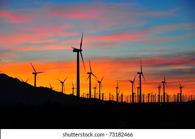 Power generating windmills against sunset