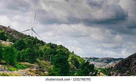 Power generators farm on rocky coast hills, wind turbines in Norway. Renewable eco energy concept.