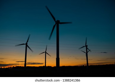 Power generators of windmills at shadow sunset - Wind turbine on field at sunset,silhouettes on dark blue night sky background