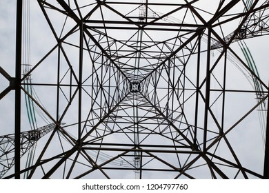 Power industry. Construct of a tall metal tower of high voltage electrical line against the sky. Bottom up view
